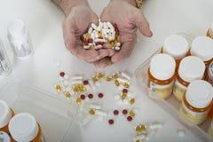 拿着药片的手围拢由药瓶 免版税库存照片