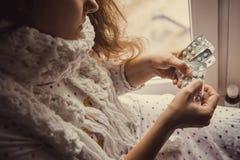 拿着药片的病的妇女手中 免版税图库摄影