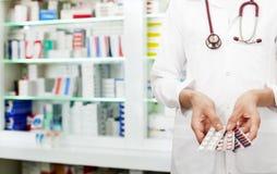 拿着药片的药剂师 免版税库存图片