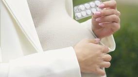拿着药片的要做妈妈的人有对采取它,怀孕的维生素的疑义 影视素材