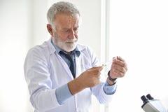 拿着药片的资深男性科学家 免版税库存图片