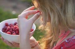 拿着莓的板材女孩,坐绿草,夏天,点心 免版税库存照片