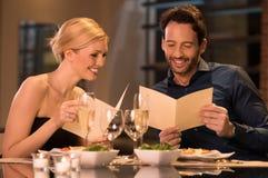 拿着菜单卡片的夫妇 免版税库存图片