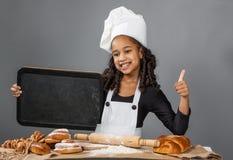 拿着菜单板的快乐的女孩厨师 免版税库存图片