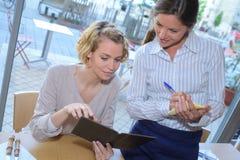 拿着菜单的年轻可爱的妇女要求女服务员 库存图片