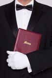 拿着菜单的等候人员在他的胳膊之下 免版税库存照片