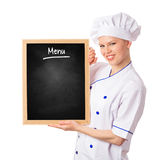 拿着菜单黑板的俏丽的微笑的厨师妇女 库存照片