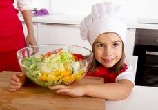 拿着菜色拉盘的红色围裙和厨师帽子的甜小女孩在家厨房 免版税库存照片
