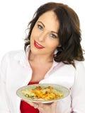 拿着菠菜和乳清干酪烤碎肉卷子面团的板材美丽的少妇 库存图片