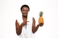拿着菠萝和指向对此的愉快的非裔美国人的妇女 库存照片