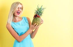 拿着菠萝的愉快的少妇 免版税库存照片