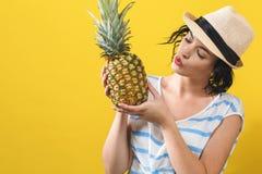 拿着菠萝的愉快的年轻女人 免版税库存图片