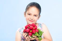 拿着萝卜的快乐的白种人小女孩 库存图片