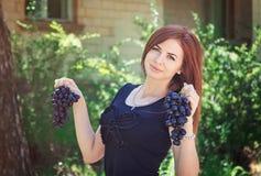 拿着葡萄束的雍妇女 库存照片
