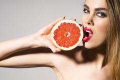 拿着葡萄柚和tuoching他的魅力女孩与嘴唇 免版税库存照片