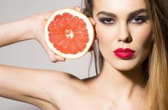 拿着葡萄柚的俏丽的女孩在头旁边切成了两半 免版税库存照片