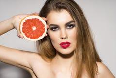 拿着葡萄柚的俏丽的魅力女孩 免版税库存图片