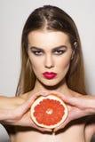 拿着葡萄柚的魅力女孩 免版税库存照片