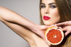 拿着葡萄柚的Preatty女孩在头旁边切成了两半 库存图片