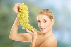 拿着葡萄的裸体妇女侧视图 免版税库存图片