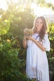 拿着葡萄的年轻美丽的妇女画象  库存照片