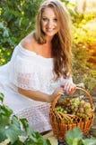 拿着葡萄的年轻美丽的妇女画象  免版税库存图片
