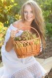 拿着葡萄的年轻美丽的妇女画象  免版税图库摄影