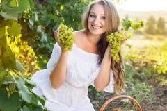 拿着葡萄的年轻美丽的妇女画象  库存图片
