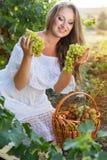 拿着葡萄的年轻美丽的妇女画象  免版税库存照片