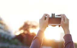 拿着葡萄酒影片照相机的妇女拍在自然日落的照片 图库摄影