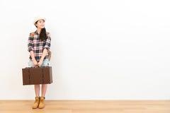 拿着葡萄酒手提箱的微笑的旅客妇女 免版税库存照片