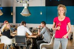 拿着葡萄酒杯的美丽的妇女在咖啡馆 免版税图库摄影