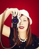 拿着葡萄酒照相机的女孩的Pin。红色背景。 免版税库存图片