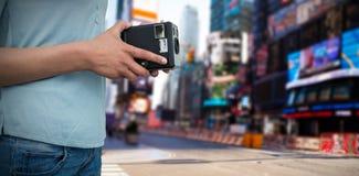 拿着葡萄酒照相机的摄影师的中间部分的综合图象 免版税库存照片