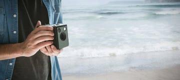 拿着葡萄酒照相机的摄影师的中间部分的综合图象 库存照片