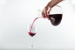 拿着蒸馏瓶和倒红葡萄酒的人播种的射击入玻璃 图库摄影