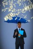 拿着蓝色伞和文件的严肃的商人画象的综合图象 免版税库存照片