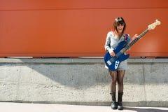拿着蓝色低音吉他的笑的妇女外面 免版税库存照片