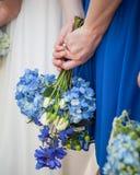 拿着蓝色八仙花属花束的女傧相反对她的在她后的蓝色礼服  免版税库存照片