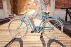 拿着蓝色减速火箭的自行车的无法认出的妇女 免版税库存照片