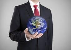 拿着蓝色地球的商人 库存照片
