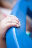 拿着蓝色塑料结构的孩子手 免版税库存图片