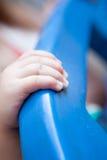 拿着蓝色塑料结构的孩子手 免版税库存照片