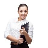 拿着蓝色日志的微笑的年轻女商人 免版税图库摄影