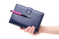 拿着蓝色皮革笔记本的手 图库摄影