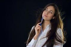 拿着蓝色笔的美丽的妇女 免版税库存照片