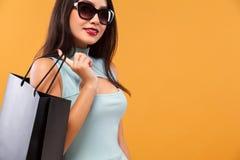 拿着蓝色袋子的购物的愉快的亚裔妇女被隔绝在橙色背景黑星期五假日 复制空间为 免版税库存图片
