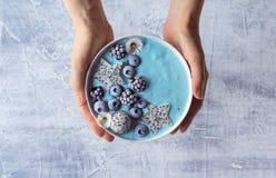 拿着蓝色酸奶莓果圆滑的人碗的手 免版税库存照片