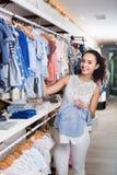 拿着蓝色婴儿衣裳的年轻快乐的妇女 免版税图库摄影