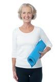 拿着蓝色锻炼席子的体育教师 库存图片